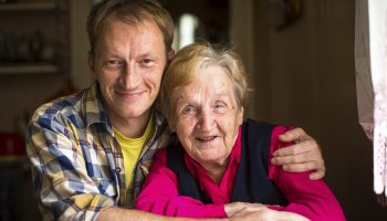 man with arm around older woman