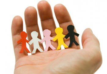 hand with paper cut outs of children in - protecting