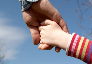 adult hand holding childs hand