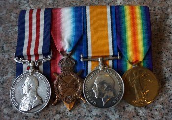 Image: photograph of four WW1 service medals with coloured ribbons