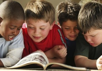 Four children reading a book