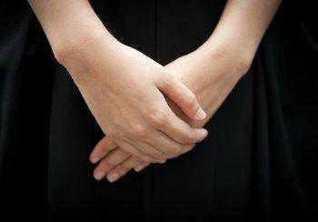 hands crossed on black skirt