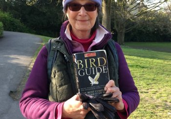 Lucy Starling looks at the camera, holding a bird ID book with binoculars around her neck and lots of bird badges on her hat