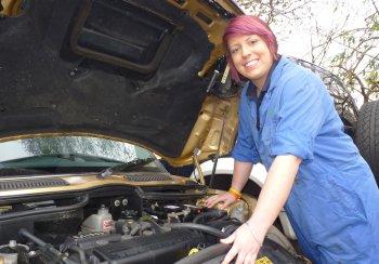 young apprentice under car bonnet