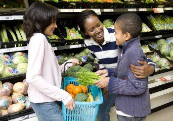 Woman and two children choosing veg at a supermarket