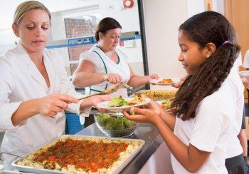 A Girl being served school dinner