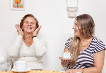 two women - one older and one younger having cuppa and chat