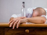 Image of man with head on a bar after drinking too much