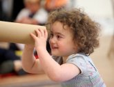 A child looking through a cardboard tube