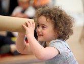A child looking through a cardboard tube