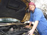 young apprentice under car bonnet