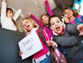 group of children with schools out sign
